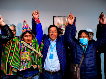 Bolivia's leftist presidential candidate Luis Arce (C), of the Movement for Socialism party, celebrates with running mate David Choquehuanca (R) early on October 19, 2020, in La Paz, Bolivia. - Bolivian presidential candidate Luis Arce, the leftist heir to former leader Evo Morales, appeared headed to a first-round election victory …