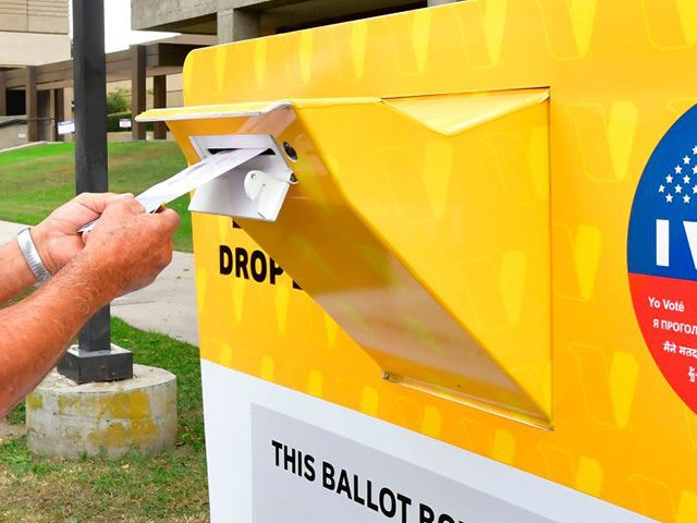 A voter drops his ballot for the 2020 US elections into an official ballot drop box at the Los Angeles County Registrar in Norwalk, California on October 19, 2020. - Voter turnout is ten times higher than in 2016 in California according the Secretary of State Alex Padilla as over …