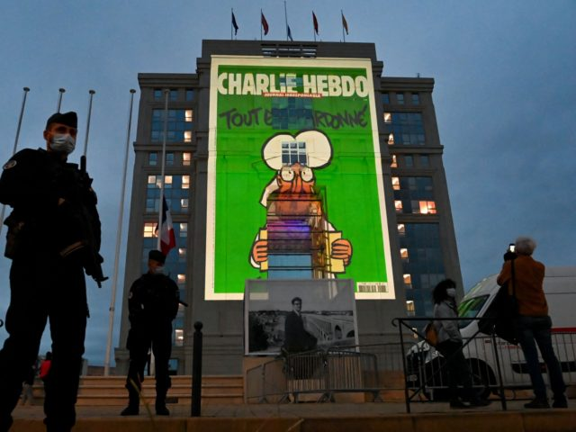 Police officers stand guard as cartoons of French satirical weekly newspaper Charlie Hebdo are projected onto the facade of the Hotel de Region in Montpellier, on October 21, 2020, during a national homage to French teacher Samuel Paty who was beheaded for showing cartoons of the Prophet Mohamed in his …