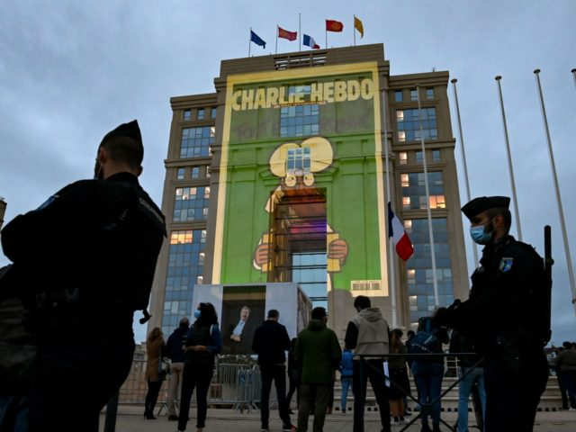 People look at cartoons of French satirical weekly newspaper Charlie Hebdo projected onto the facade of the Hotel de Region in Montpellier, on October 21, 2020, during a national homage to French teacher Samuel Paty who was beheaded for showing cartoons of the Prophet Mohamed in his civics class. - …