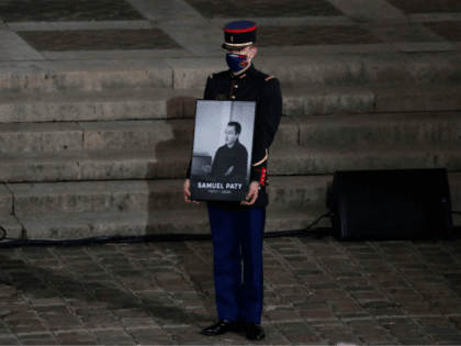 A French Republican Guard holds a portrait inside Sorbonne University's courtyard in Paris on October 21, 2020, during a national homage to French teacher Samuel Paty, who was beheaded for showing cartoons of the Prophet Mohamed in his civics class. - France pays tribute on October 21 to a history …