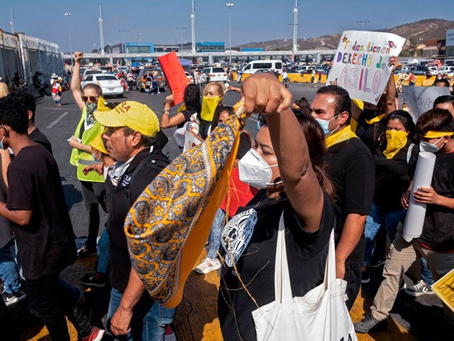 Migrants and human rights activists protest against US and Mexican migration policies at the San Ysidro crossing port, in Tijuana, Baja California state, Mexico, on the border with the US, on October 21, 2020, amid the new coropnavirus pandemic. - With the implementation of the Migrant Protection Protocol (MPP), asylum …