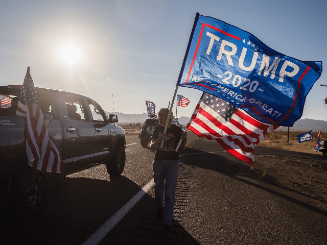 A woman waves a Trump and a US National flag as a caravan of cars from Kingman drives past supporting President Trump, as they gather for a presidential debate watch party, in Golden Valley, Arizona on October 22, 2020. (Photo by ARIANA DREHSLER / AFP) (Photo by ARIANA DREHSLER/AFP via …
