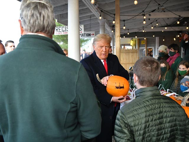 US President Donald Trump(C) signs some pumpkins as he meets with people at Treworgy Orchards during a campaign stop in Levant, Maine on October 25, 2020. - In a single day, he covered more than 3,000 kilometers (1,800 miles) aboard Air Force One, hitting three different campaign rallies from the country's south to the midwest. And Donald Trump has shown his willingness to keep up the frenetic pace he set on October 24, 2020 all the way until the November 3 election. (Photo by MANDEL NGAN / AFP) (Photo by MANDEL NGAN/AFP via Getty Images)
