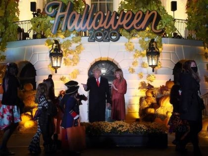 US President Donald Trump and First Lady Melania Trump greet trick or treaters during a Halloween celebration at the White House in Washington, DC, on October 25, 2020. - Due to Covid-19 the President and First Lady did not hand out actual candy to children, bags of goodies were set …