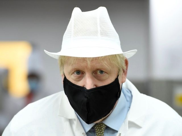 Britain's Prime Minister Boris Johnson, wearing a face mask or covering due to the COVID-19 pandemic, reacts during his visit to Royal Berkshire NHS Hospital in Reading, west of London on October 26, 2020, to mark the publication of a new review into hospital food. (Photo by Jeremy Selwyn / …