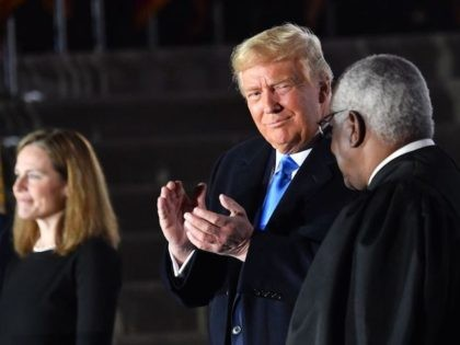 US President Donald Trump applauds next to Supreme Court Associate Justice Clarence Thomas and judge Amy Coney Barrett who was just sworn-in as a US Supreme Court Associate Justice, during a ceremony on the South Lawn of the White House October 26, 2020, in Washington, DC. (Photo by Nicholas Kamm …