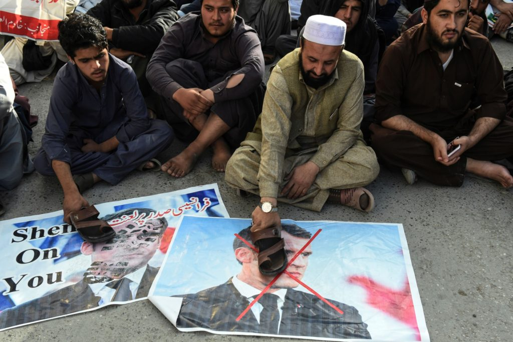 Muslims demonstrators put slippers over posters with the picture of French President Emmanuel Macron during a protest following Macron's comments over the Prophet Mohammed caricatures, in Quetta on October 29, 2020. (Photo by Banaras KHAN / AFP) (Photo by BANARAS KHAN/AFP via Getty Images)