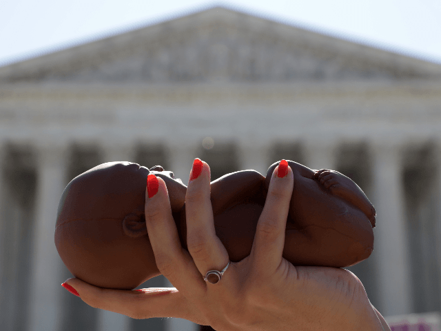 A pro-life activist holds a model fetus during a demonstration in front of the U.S. Supreme Court June 29, 2020 in Washington, DC. The Supreme Court has ruled today, in a 5-4 decision, a Louisiana law that required abortion doctors need admitting privileges to nearby hospitals unconstitutional. (Photo by Alex Wong/Getty Images)