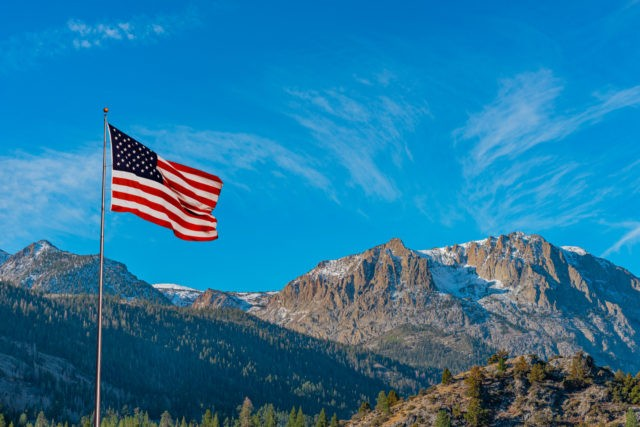 An American flag flies over the Californian Sierra Nevada mountains in the Gull Lake area of California. The lake area is on the June Lake Loop.