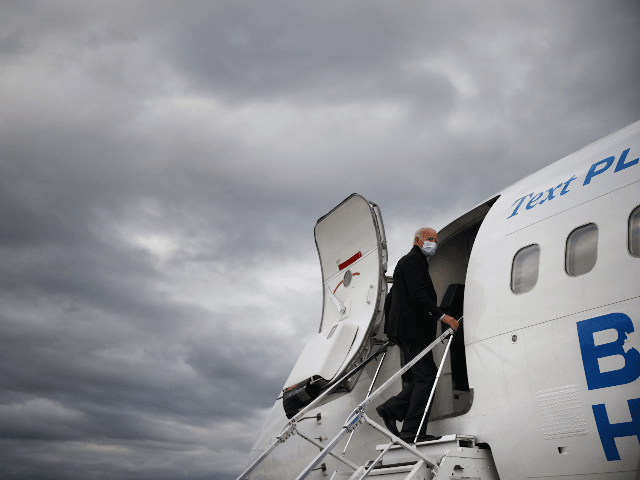 Wearing a mask to reduce the risk posed by the coronavirus, Democratic presidential nominee Joe Biden boards his plane at Gerald Ford Airport after campaigning October 02, 2020 in Grand Rapids, Michigan. Biden said he tested negative twice Friday for the coronavirus after it was reported that U.S. President Donald …
