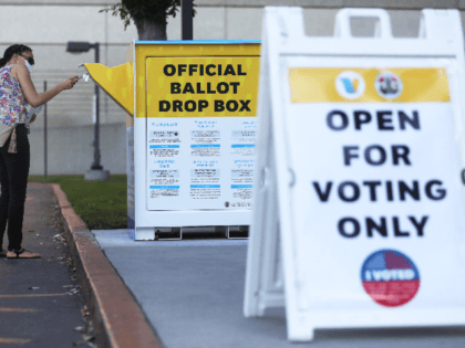 A pedestrian places a ballot in an official mail-in ballot drop box outside of the L.A. County Registrar's office ahead of Election Day on October 14, 2020 in Norwalk, California. Over 1 million Californians have returned their mail-in ballots with Election Day over two weeks away, breaking the record for …