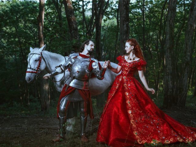 Medieval knight with his beloved lady in red dress