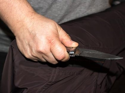 Closeup of a young man hand, holding a knife, about to attack,
