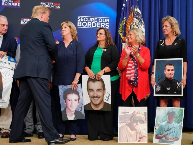 US President Donald Trump greets people holding posters of people allegedly killed by illegal immigrants before speakong on immigration in the South Court Auditorium, next to the White House on June 22, 2018 in Washington, DC. (Photo by Mandel NGAN / AFP) (Photo credit should read MANDEL NGAN/AFP via Getty …