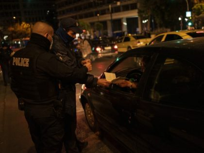 A police officer checks the documents of a driver verifying permission of movement in Athens on October 25, 2020. - Greek Prime Minister Kyriakos Mitsotakis on October 23 declared a night curfew in Athens, Thessaloniki and other areas to curb the spread of the novel coronavirus. (Photo by Angelos Tzortzinis …
