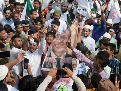 Muslim demonstrators shout slogans as they hold a poster of French President Emmanuel Macron during a protest calling for the boycott of French products and denouncing Macron for his comments over the Prophet Mohammed caricatures, in Hyderabad on October 30, 2020. (Photo by NOAH SEELAM / AFP) (Photo by NOAH …