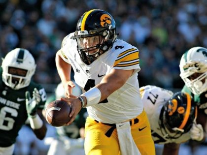 In this Sept. 30, 2017, file photo, Iowa quarterback Nate Stanley, center, looks to hand off against Michigan State's Brandon Randle, left, and Raequan Williams, right, during the second quarter of an NCAA college football game in East Lansing, Mich. Stanley is playing well, just in time for a trip …
