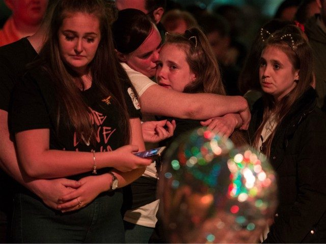 People grieve during a silence at 10:31pm, the exact one year anniversary of the deadly attack at Manchester Arena, central Manchester on May 22, 2018. - Prime Minister Theresa May and Prince William will on May 22, 2018 join families of the victims of the Manchester Arena bombing at a …