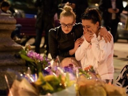 MANCHESTER, ENGLAND - MAY 23: A woman is consoled as she looks at the floral tributes following an evening vigil outside the Town Hall on May 23, 2017 in Manchester, England. An explosion occurred at Manchester Arena as concert goers were leaving the venue after Ariana Grande had performed. Greater …