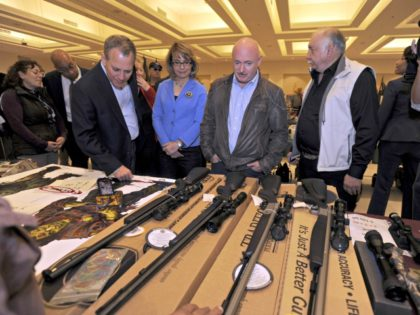 New York Attorney General Eric Schneiderman, former U.S. Rep Gabrielle Giffords, and her husband Mark Kelly, along with show organizer Dave Petronis, right, tour the New Eastcoast Arms Collectors Associates arms fair in Saratoga Springs, N.Y. on Sunday, Oct. 13, 2013. They are looking at a display of muzzle loaders. …