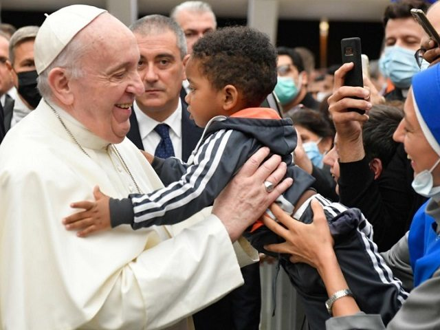 Pope Francis hugs child at General Audience