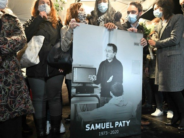 Relatives and colleagues hold a picture of Samuel Paty during the 'Marche Blanche' in Conflans-Sainte-Honorine, northwest of Paris, on October 20, 2020, in solidarity after a teacher was beheaded for showing pupils cartoons of the Prophet Mohammed. His murder in a Paris suburb on October 16 shocked the country and …