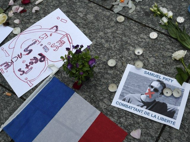 "A photo shows a placard with the portrait of history teacher Samuel Paty and reading ""Freedom fighter"" as people gather in Strasbourg, eastern France, on October 18, 2020, to two days after he was beheaded by an attacker who was shot dead by policemen. - Thousands of people rally in …"
