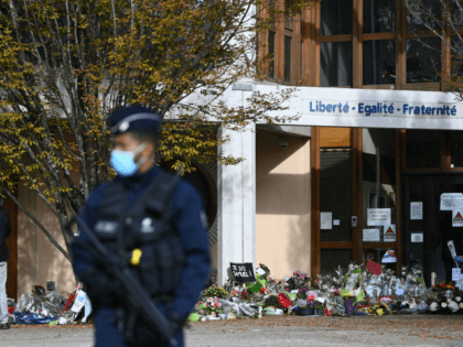 People look at flowers layed outside the Bois d'Aulne secondary school in homage to slain history teacher Samuel Paty, who was beheaded by an attacker for showing pupils cartoons of the Prophet Mohammed in his civics class, on October 19, 2020, in Conflans-Sainte-Honorine, northwest of Paris. - Paty, 47, was …