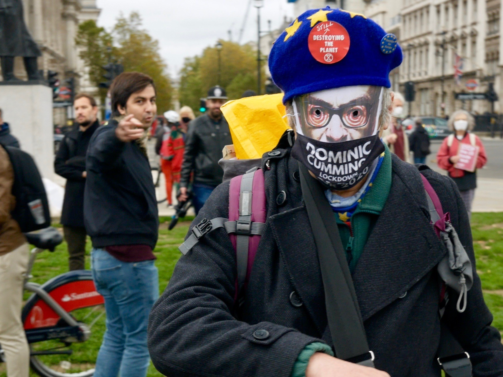 A man poses in a Dominic Cummings mask and EU cap at the Stop Trump Coalition Protest in London, October 24, 2020. Kurt Zindulka, Breitbart News