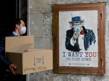 """A man wearing a face mask walks past a poster by artist TVBoy featuring Uncle Sam and reading """"I want you to stay home"""" in Barcelona on March 14, 2020 after regional authorities ordered all shops in the region be shuttered from today through March 26, save for those selling …"""