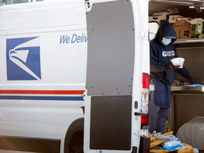 A mailman wearing a mask and gloves to protect himself and others from COVID-19, known as coronavirus, loads a postal truck with packages at a United States Postal Service (USPS) post office location in Washington, DC, April 16, 2020. - For many Americans, checking the mailbox is a daily ritual, …