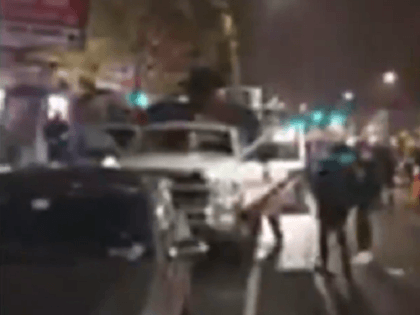 Philadelphia rioters vandalize and loot vehicles.