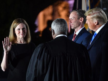 US President Donald Trump watches as Supreme Court Associate Justice Clarence Thomas swears in Amy Coney Barrett as a US Supreme Court Associate Justice, flanked by her husband Jesse M. Barrett, during a ceremony on the South Lawn of the White House October 26, 2020, in Washington, DC. (Photo by …