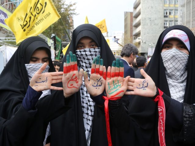 Iranian women display religious symbols written on the palms of their hands during a demonstration outside the former US embassy in the Iranian capital Tehran on November 4, 2019, to mark the 40th anniversary of the Iran hostage crisis. - On November 4, 1979, less than nine months after the …