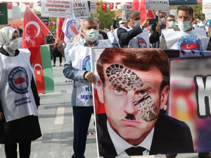 Men hold a sign bearing a picture of French President Emmanuel Macron with a shoe print on it as Turkish protesters shout slogans during a demonstration against French President's comments over Prophet Muhammad cartoons, in Ankara, on October 27, 2020. - Muslims across the world have reacted furiously to Macron's …