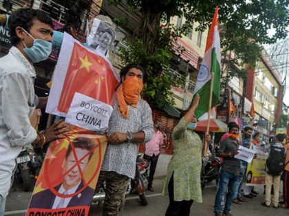 "Activists of Bharatiya Janata Party (BJP) stand in line as they prepare to burn an effigy of Chinese President Xi Jinping during an anti-China protest in Siliguri on June 17, 2020. - India and China held top level talks on June 17 to ""cool down the situation"", Beijing said, after …"