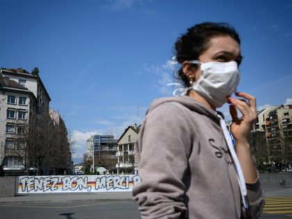 "TOPSHOT - A woman wearing a protective face mask walks by a giant banner reading : ""Hold on, thank you for everything"" deployed in front of the Geneva University Hospitals (HUG) as a lockdown is in effect to prevent the spread of the COVID-19 caused by the novel coronavirus, in …"