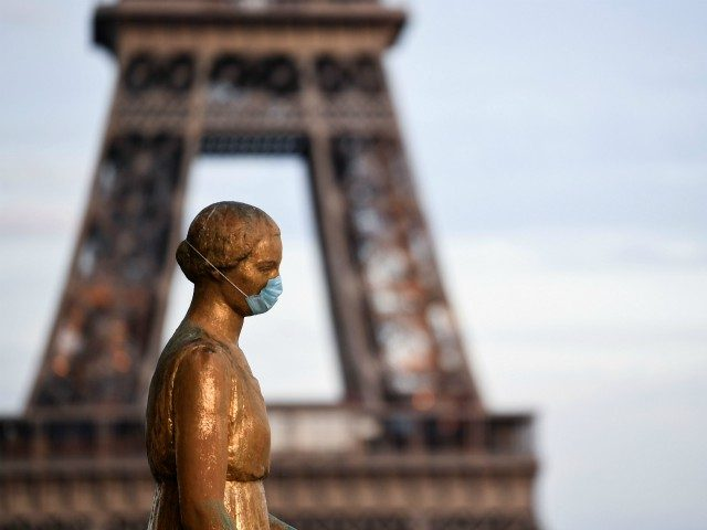 A picture taken on May 2, 2020 shows a bronze statue wearing a face mask emmulating the actions of many citizens to protecting themselves against the novel coronavirus, COVID-19 at the Parvis des Droits de l'Homme, with the Eiffel Tower in background in Paris, on the 47th day of a …