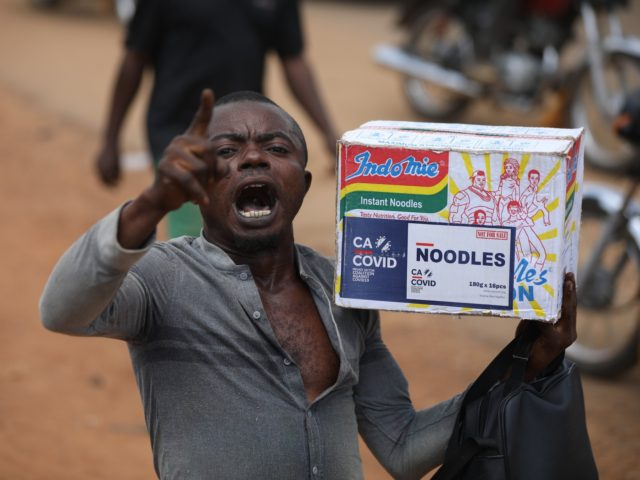 A man reacts while carrying a bag of noodles during a mass looting of a warehouse that have COVID-19 food palliatives that were not given during lockdown to relieve people of hunger, in Abuja, Nigeria, on October 26, 2020. - Nigeria, with 200 million inhabitants, counts the highest number of …