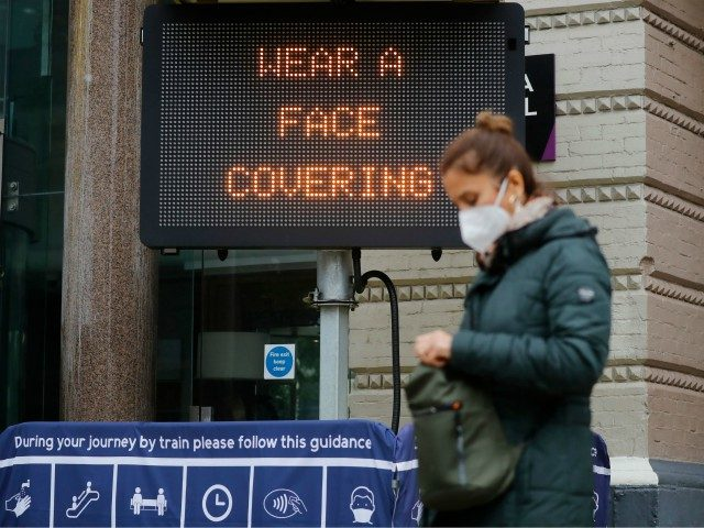 A pedestrian walks past a sign displaying a message to wear a face covering, outside Charing Cross station in central London on October 14, 2020, as the number of cases continue to rise during the novel coronavirus COVID-19 pandemic - Prime Minister Boris Johnson on Wednesday said a new UK-wide …