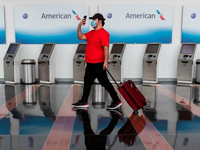 A passenger walks past empty American Airlines check-in terminals at Ronald Reagan Washington National Airport in Arlington, Virginia, on May 12, 2020. - The airline industry has been hit hard by the COVID-19 pandemic, with the number of people flying having decreased by more than 90 percent since the beginning …