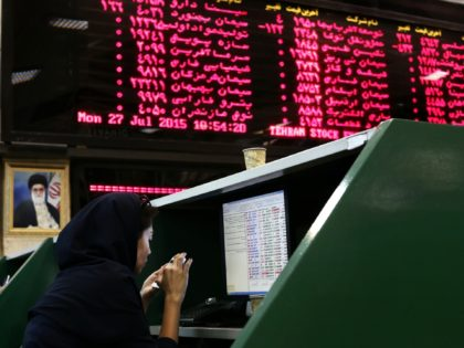 An Iranian dealer checks her mobile phone next to stock market activity boards at the stock exchange in the capital Tehran on July 27, 2015. Iran's central bank chief said that Iran has assets of $29 billion in overseas banks that could be unlocked under a nuclear deal struck on …