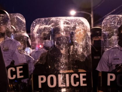 Police in riot gear face protesters marching through West Philadelphia on October 27, 2020, during a demonstration against the fatal shooting of 27-year-old Walter Wallace, a Black man, by police. - Hundreds of people demonstrated in Philadelphia late on October 27, with looting and violence breaking out in a second …