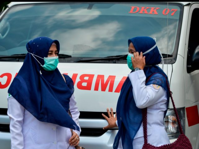 Indonesian medics wearing face masks stand in front of an ambulance in Banda Aceh on March 2, 2020. - Indonesia on March 2 reported its first confirmed case of coronavirus, after health officials in the world's fourth-most populous country hit back at questions over its apparent lack of infected patients. …