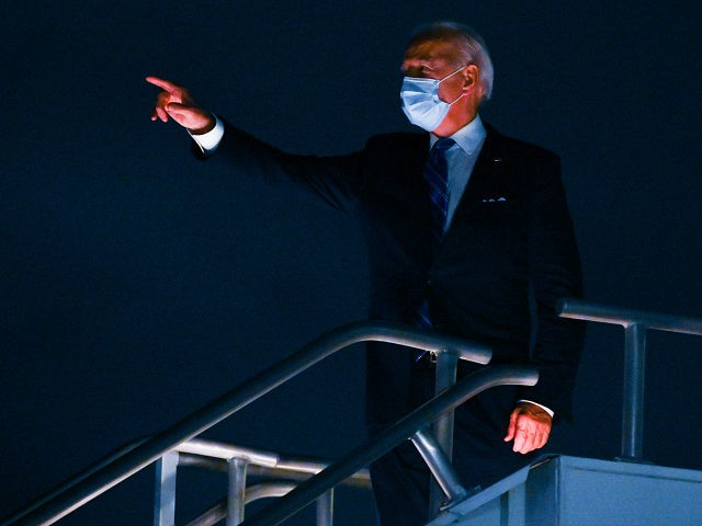 Democratic presidential nominee and former Vice President Joe Biden, wearing a facemask, acknowledges authority escorts lined nearby before taking off from Miami International Airport in Miami, Florida to head back to his hometown of Wilmington, Delaware after having participated in a Town Hall meeting on October 5, 2020. (Photo by …
