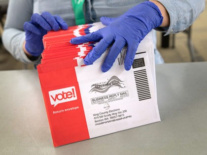 RENTON, WASHINGTON - MARCH 09: An election worker wearing protective gloves sorts through mailed-in ballots in the King County Elections ballot processing center on March 09, 2020 in Renton, Washington. Election officials mandated the precautionary measure for workers handling ballots in this year's primary election counting process. King County has …