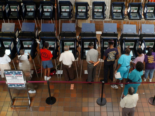 Residents of Dade County work electronic voting machines at a local voting station in Miami 18 October 2004. The electronic voting machines are new in Florida, having replaced the punch-card system, four years after the state was ground zero in the US election debacle resolved in favour of Bush by …