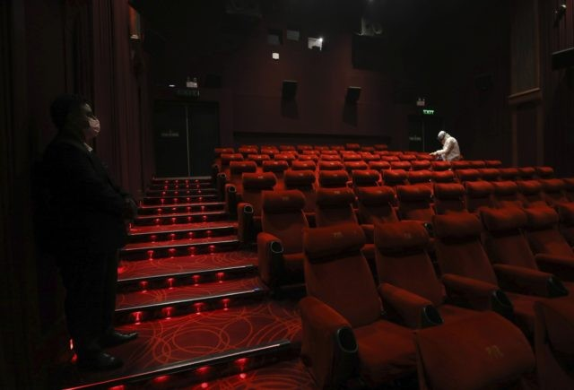 In this Friday, July 31, 2020, file photo, a worker of PVR cinemas, a multiplex cinema chain, sanitizes a theater during a press preview to show their preparedness to handle the COVID-19 pandemic in New Delhi, India. After seven months of total blackout, cinemas reopened Thursday, Oct. 15, in several …