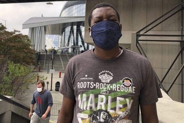 In this Oct. 15, 2020, photo Tunde Ezekiel poses for a photo after voting early at State Farm Arena in downtown Atlanta. A Democrat, Ezekiel said he came out to vote early to avoid Election Day lines and to ensure that his vote against President Donald Trump is counted. (AP …